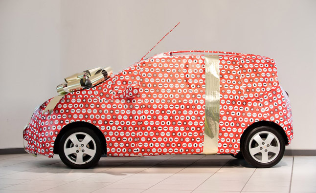 small rideshare vehicle covered in wrapping paper for Christmas