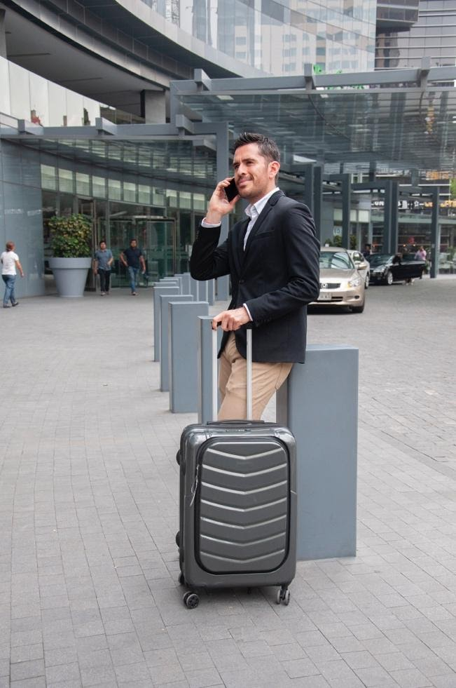 A person holding a piece of luggage Description automatically generated